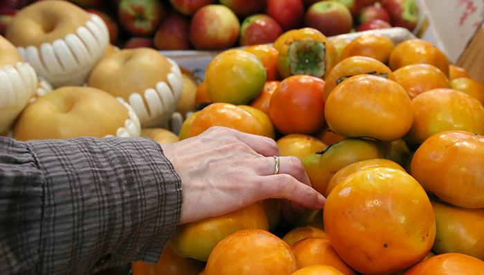 망원시장 내 과일가게를 찾은 손님들이 사과와 감을 고르고 있다. 농촌진흥청은 평년보다 20% 이상 많은 일조량을 기록했던 올해는 그 어느 해보다 맛있는 과일을 맛 볼 수 있다고 밝혔다.