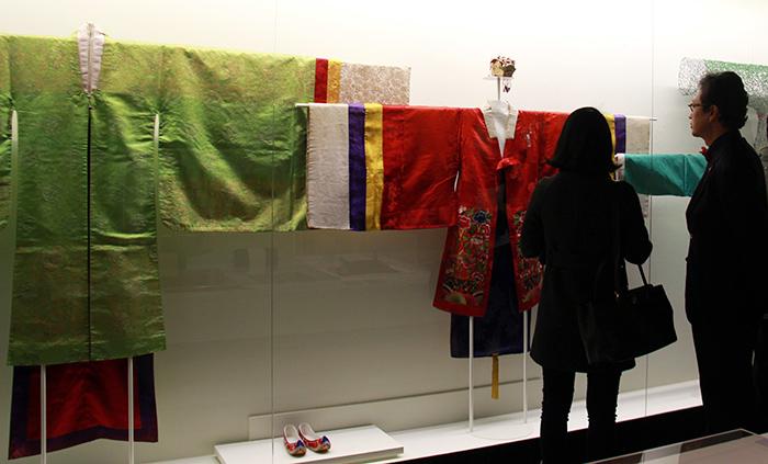 '배색' 전시에서는 음과 양을 적절히 조화하면 복을 얻을 수 있다는 선조들의 믿음과 관련된 유물이 소개됐다. 관람객들이 붉은 색과 푸른 색의 배색이 특징인 전통혼례복을 살펴보는 모습.
