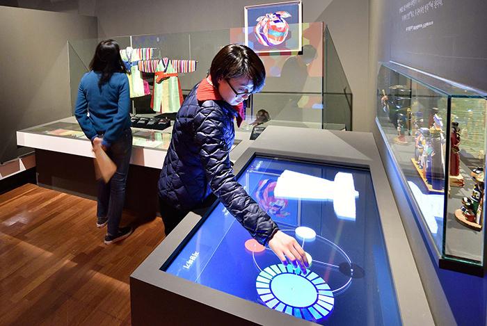 '때깔전'에서는 영상 기기를 통해 색의 배색과 조화를 체험할 수 있다. 관람객이 영상기기를 이용해 직접 색을 선택해서 자신만의 가상 색동한복을 만들어보는 모습.