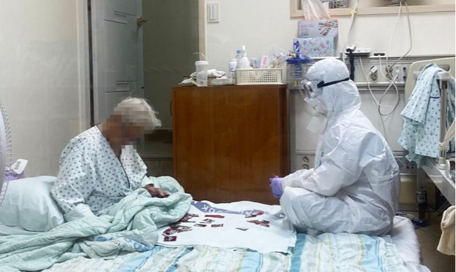 국민들 감동시킨 '방호복 입고 할머니와 화투놀이하는 간호사' 사진